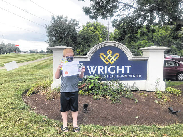 """""""Healthcare Angel"""" essay contest winner Mason Gilliam stands outside Wright Rehabilitation and Healthcare Center."""