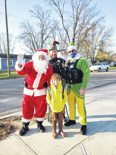 Santa and two of his elves (otherwise known as SROs Wes Frederick, Tyler McCarty and Zach Zink) pose with a Fairborn Primary student.