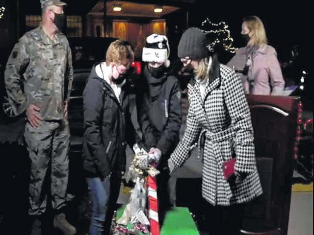 The family of a deployed member of the 88th Medical Group flipped the switch for the Wright-Patterson holiday tree lighting, to the tune of cheers and honking horns from attendees.