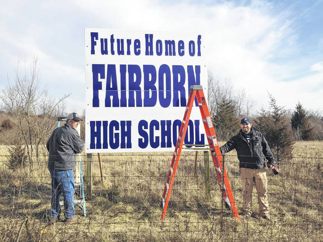 Crews put up signs at the property on Commerce Center Boulevard where the new Fairborn High School will be built.