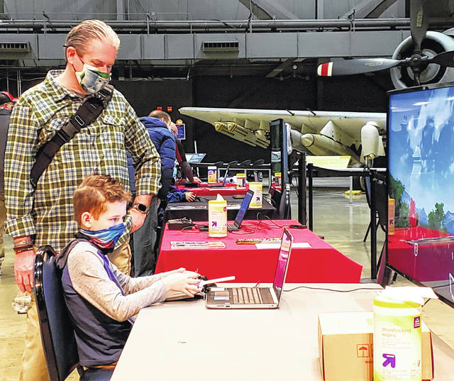 A boy tests his skills using a Sinclair drone flying simulator Saturday.