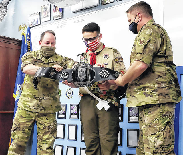 Sgt. Chuck Muston and Maj. Erik Fricsons present junior Jonathan Woodward with a JROTC-themed championship wrestling belt. Woodward, a huge WWE fan, presented his Eagle Scout project to his JROTC peers Wednesday.