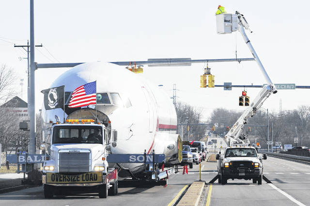 Electrical crews lift up wires and traffic signals just enough for the huge fuselage of a Boeing 767 aircraft to slip underneath on Dayton-Yellow Springs Rd. The fuselage traveled through Fairborn on the last leg of its journey from Wilmington Air Park to Wright Patterson AFB.