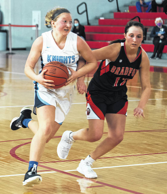 Legacy Christian Academy senior Margaret Kensinger drives to the basket as Bradford's Cassi Mead tries to guard her. Kensinger had a big first half to help the Knights win a Division-IV district title.