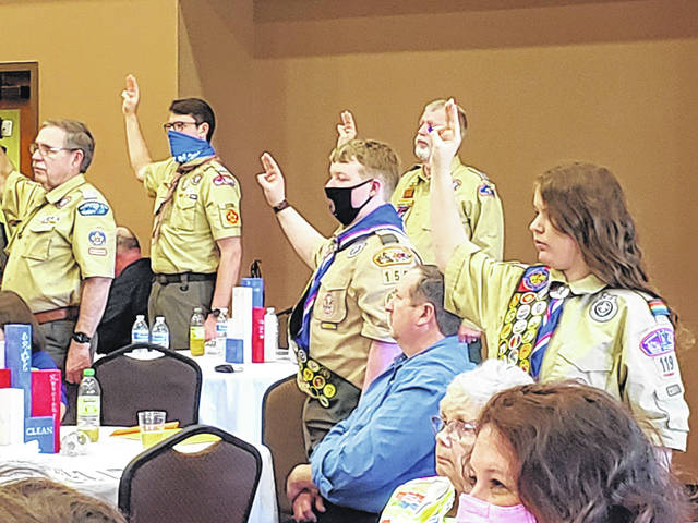 Scouts of all generations, including Kylee Dutenhaber (front), renew their scouting oath during the NESA Luncheon Sunday.
