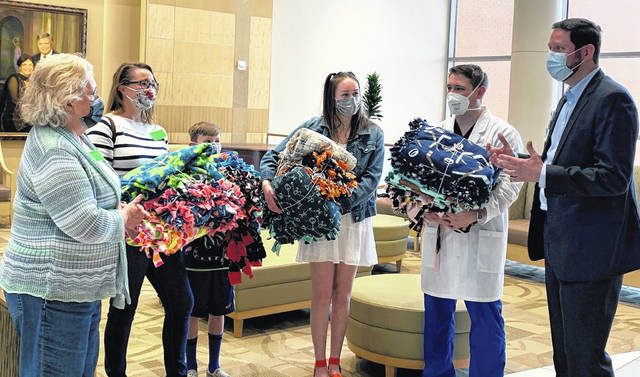 Eighth grade students at Olentangy Berkshire Middle School near Columbus made blankets and donated them to Soin Medical Center. The mother of teacher Jennifer Ebersole was a patient at Soin and she wanted to do something to show her appreciation for the care she received. Among those pictured are Ebersole, her mother, Portia Hammond, Ebersole's children, and Soin President Rick Dodds.