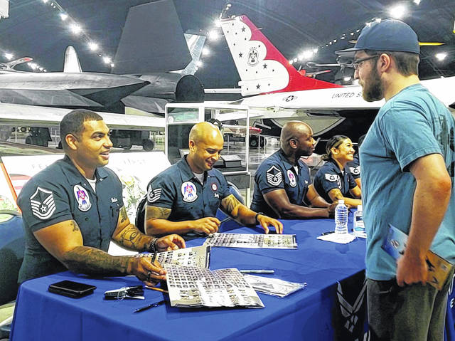 Thunderbird pilots and crew members sign posters and memorabilia of visitors to the Air Force Museum Friday morning. The Thunderbirds headline the Dayton Air Show this weekend at Dayton International Airport. Doors open at 9 a.m.