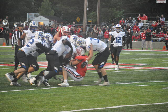 A group of Xenia defenders stuff this run attempt in the first half by Tippecanoe. The Red Devils prevailed in a 30-0 win.
