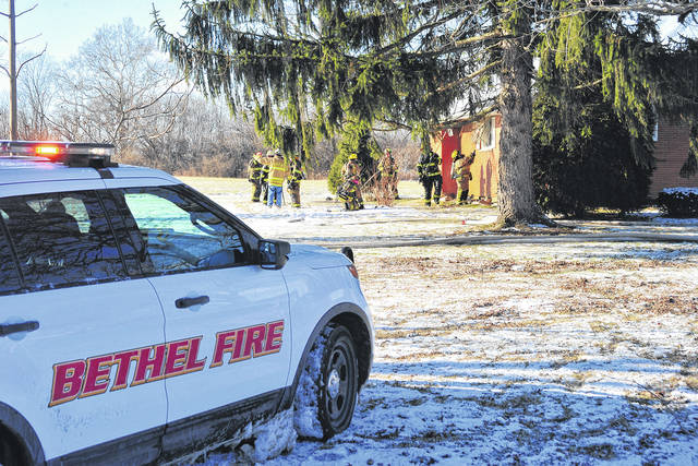 Mike Ullery | Daily Call Firefighters work to access a fire through the eves of a home in the 7000 block of Palmer Road in Bethel Twp. on Christmas day.