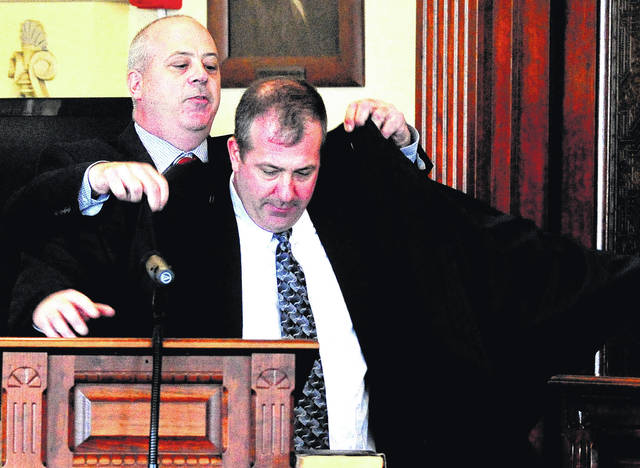 Mike Ullery | Daily Call Rep. Steve Huffman of the Ohio House of Representatives District 80, helps his brother, newly sworn Miami County Municipal Court Judge Sam Huffman, into his robe following his swearing-in ceremony at the Miami County Courthouse on Friday.