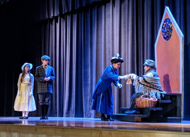 Cecilia Fox | Weekly Record Herald Mary Poppins, junior Samantha del Rosario, teaches the Banks children, Alaina Yarwick and Ean Bosma, the value of a tuppence by buying a bag of crumbs from Bird Woman, Sophia Yarwick, in Bethel High School's production of Mary Poppins. The show ran from Thursday through Saturday.