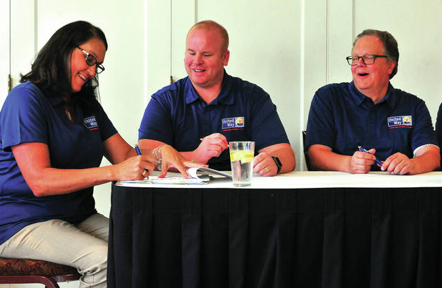 Mike Ullery | AIM Media Midwest United Way board member Lisa McGraw adds her signature to a document merging United Way chapters in Piqua, Troy, and Tipp City into a single Miami County United Way chapter during a press conference at the Troy Country Club on Thursday morning. Looking on are Sean Ford, executive director of Miami County United Way, center, and board member Andrew Wannamacher.