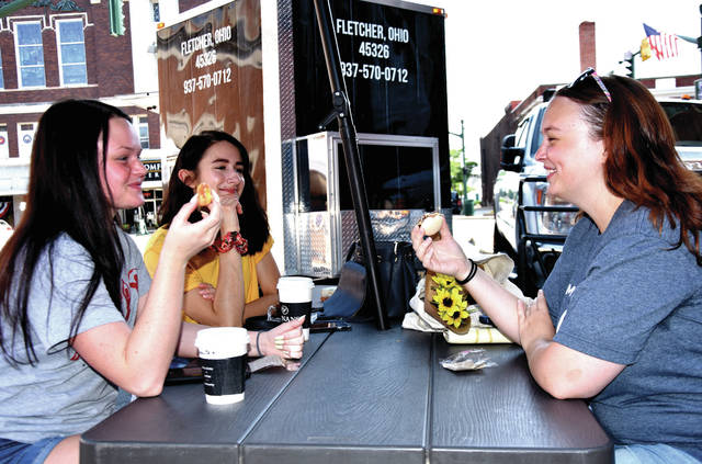 Cody Willoughby | Troy Daily News Jillian Blount, Lydia Shigley, and Samantha Martin of Troy enjoy confections in the shade during the Downtown Troy Farmer's Market on Saturday, June 16.