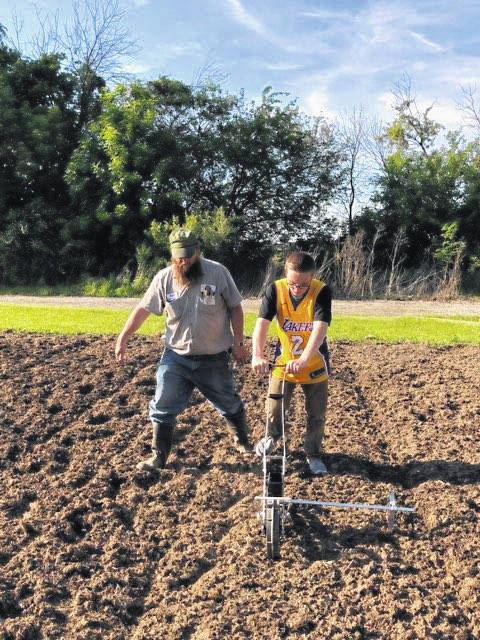 Daniel Oldham helps Anthony Putnam plant popcorn at the A.B. Graham Center on June 10. Putnam is a member of the Mr. Graham's Museum 4-H club. The center is hosting a 150th birthday party in honor the founder of the 4-H club, A.B. Graham, who was born in Lena.