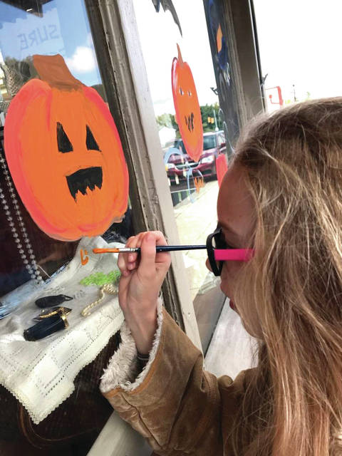 Provided photo Lily Brazie works on a jack-o'-lantern painted on a window of the Treasure Chest in West Milton.