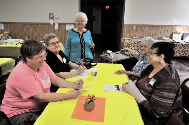 Cecilia Fox | AIM Media Julie Segi, Karen Foster, Sadie Thiele and Pam Schmidt are regulars at the center and they encourage more residents of all ages to stop by and check out the events. Roberta Imes, standing, stopped by Sunday to visit friends. Cecilia Fox | AIM Media Activities Director Carol Garver shows off some of the scrapbooks of pictures and clippings collected during the center's history.