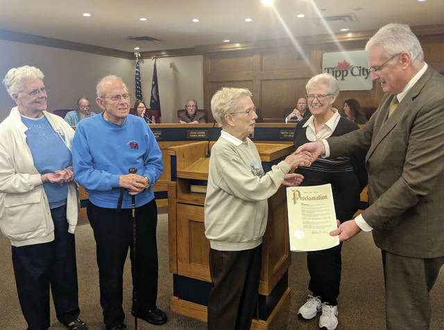 Cecilia Fox | Weekly Record Herald Mayor Joe Gibson, right, presents a proclamation from the council to Tipp City Seniors President Ruth Reinhard and senior center building committee chairman John Berk.