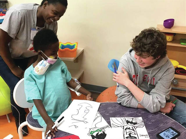 Provided photo Oskey said this moment spent drawing Batman characters with a patient at Dayton Children's last fall was one of his favorites.