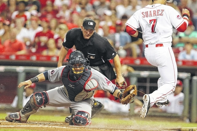AP photo The Reds' Eugenio Suarez (7) leaps to avoid the tag by Cleveland's Yan Gomes (10) to score during Friday's game in Cincinnati.