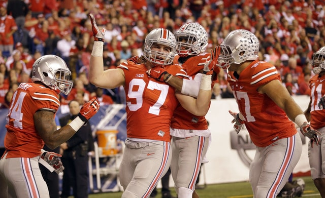 In this Dec. 6, 2014, file photo, Ohio State defensive lineman Joey Bosa (97) is congratulated by teammates after recovering a fumble and running it back for a touchdown during the first half of the Big Ten Conference championship NCAA college football game against Wisconsin in Indianapolis. Ohio State has suspended All-America defensive end Joey Bosa, receiver Corey Smith and H-backs Jalin Marshall and Dontre Wilson for its opening game at Virginia Tech. In a statement released about an hour before Big Ten media days began Thursday, July 30, 2015, the Buckeyes said the players violated department of athletics policy.