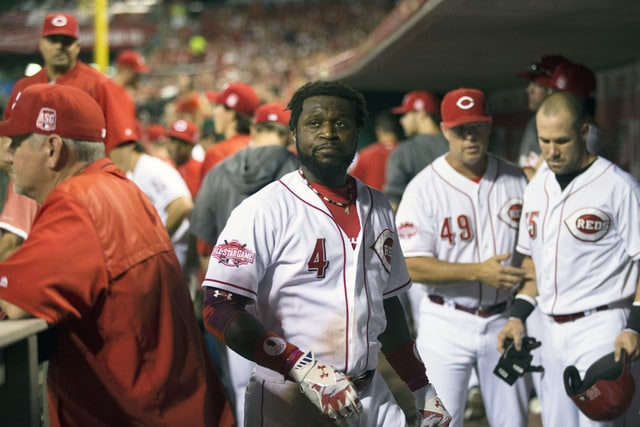 Cincinnati Reds' Brandon Phillips (4) stands in the dugout in the sixth inning after hitting his second three-run home run during a baseball game against the Pittsburgh Pirates, Thursday, July 30, 2015, in Cincinnati. (AP Photo/John Minchillo)