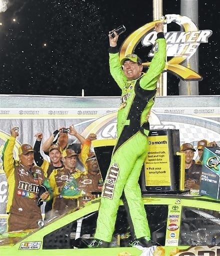 Kyle Busch celebrates on his car in Victory Lane after he won the NASCAR Sprint Cup race at Kentucky Speedway in Sparta, Ky., Saturday. AP Photo