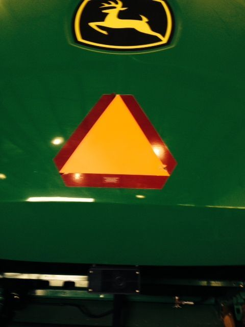 "This slow moving vehicle emblem is installed on the rear of a John Deere combine. SMVs must comply with certain federal engineering standards that are specified at ANSI/ASAE ""S276.7 (SEP 2010)""."