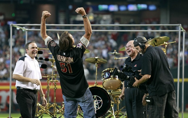 Hall of Fame pitcher Randy Johnson reacts as he is presented with a Rush 40th anniversary Neil Peart signature drum set during a ceremony retiring his No. 51 Arizona Diamondbacks jersey, before a baseball game between the Cincinnati Reds and the Diamondbacks, Saturday, Aug. 8, 2015, in Phoenix. (AP Photo/Ralph Freso)