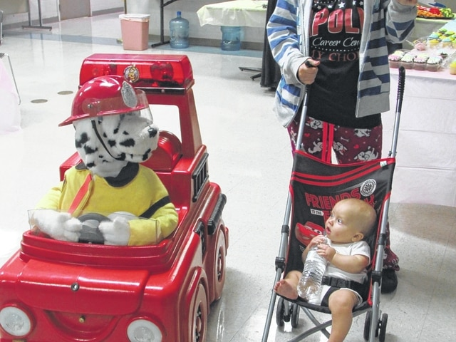 Danae King | The Lima News A Lima Fire Department fire inspector voices an animated fire dog as it speaks to a baby at the Community Baby Shower on Saturday.