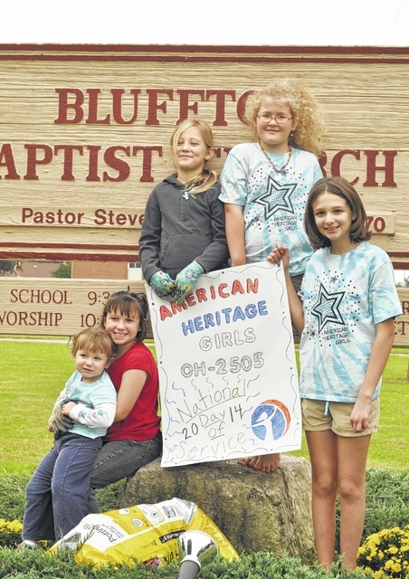 Reagan Fensler (from left), Kaylee Fensler, Lillian Dagani, Ivy Augsburger and Adelaide Kinn plant mums at Bluffton Baptist Church for their first service project.