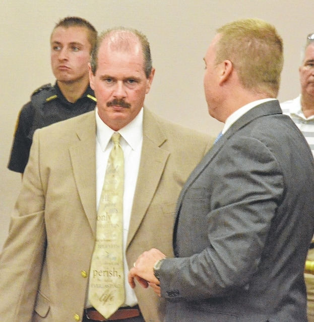 Retired Allen County Sheriff Sgt. Frederick DePalma Jr., talks with his attorneys Thursday. DePalma pleaded guilty to 59 felony charges for stealing from the agency property room.