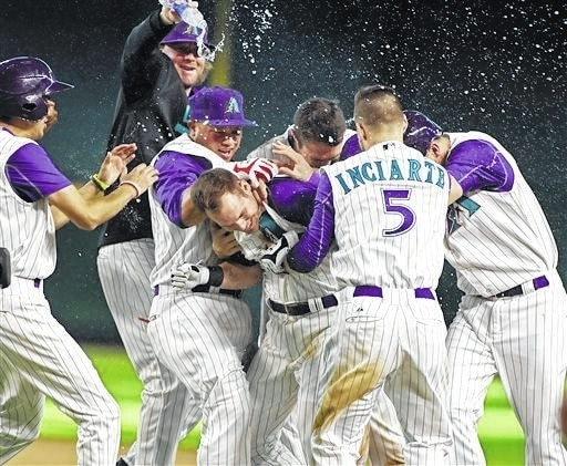 Arizona Diamondbacks' Chris Owings, center, celebrates with teammates Archie Bradley, top left, Wellington Castillo, second from left, A.J. Pollock, top center, Ender Inciarte (5) and Jake Lamb, right, after his game winning sacrifice fly against the Cincinnati Reds during the tenth inning of a baseball game, Sunday, Aug. 9, 2015, in Phoenix. The Diamondbacks won the game 4-3. (AP Photo/Ralph Freso)