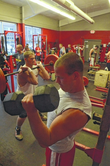 Members of the Columbus Grove football team work out in the school's weight room. Weight training helped players get bigger, stronger, faster and closer, area coaches agreed.