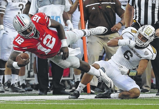 Don Speck | The Lima News Ohio State's Cardale Jones streches for a first down against Western Michigan's Asantay Brown during Saturday's game at Ohio Stadium in Columbus.