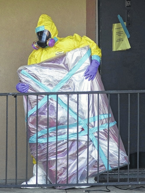 In this Oct. 6 file photo, a hazardous material cleaner removes a wrapped item from the Dallas apartment where Thomas Eric Duncan, the Ebola patient who traveled from Liberia to Dallas, stayed. Most people will experience at least one wrong or delayed diagnosis in their lifetime, concludes an alarming report that calls diagnostic errors a blind spot in modern medicine that can cause devastating consequences. (AP Photo/LM Otero, File)