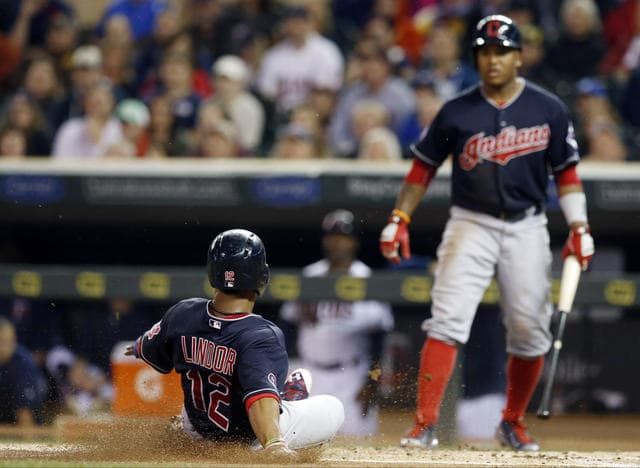 Cleveland Indians Francisco Lindor, left, scores as Jose Ramirez watches as both scored on a two-run single by Lonnie Chisenhall off Minnesota Twins pitcher Kyle Gibson in the first inning of a baseball game, Thursday, Sept. 24, 2015, in Minneapolis. (AP Photo/Jim Mone)