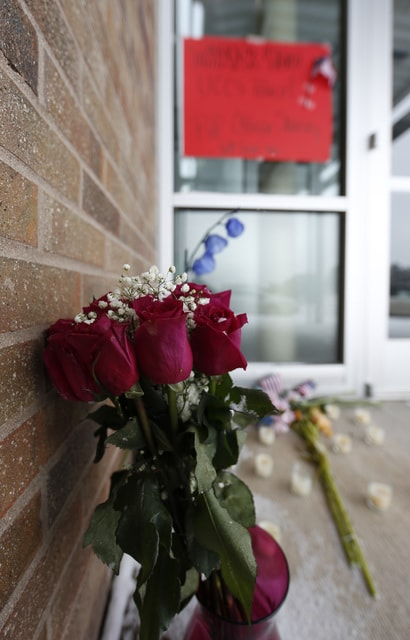 A bouquet of roses stands with other tributes to University of Colorado-Colorado Springs police officer killed during the shooting at a Planned Parenthood clinic outside the door to the public safety department on the school's campus in northwest Colorado Springs, Saturday in Colorado Springs, Colo. (AP Photo/David Zalubowski)