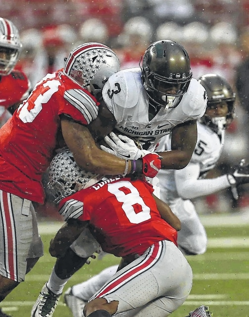 Don Speck | The Lima News Ohio State's Darron Lee, left, and Gareon Conley wrap up Michigan State's L.J. Scott during Saturday's game at Ohio Stadium in Columbus.