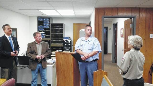 Lima postal worker Scott Eversole, third from left, was honored Thursday by the Allen County commissioners and Dog Warden Julie Shellhammer, right, for intervening in an Oct. 19 dog attack.