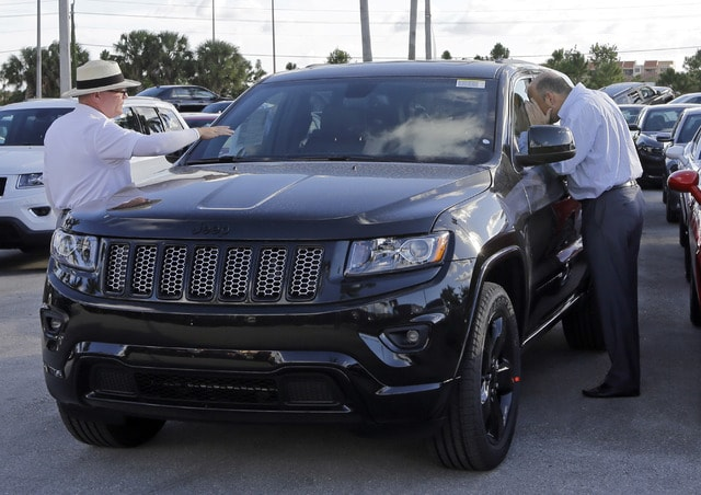 In this Nov. 5 photo, salesperson Andrew Montalvo, left, talks to a customer checking out the interior of a 2015 Grand Cherokee Limited in Doral, Fla. Fiat Chrysler sales are up in what could be a record November. (AP Photo/Alan Diaz)