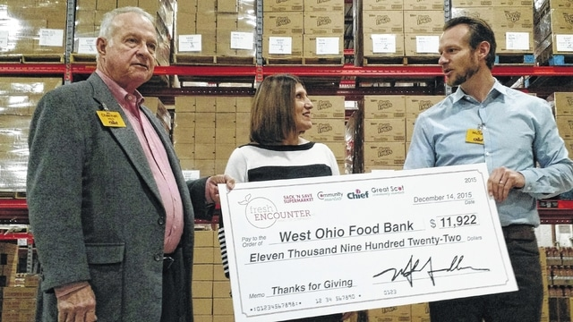 Representatives from Fresh Encounter Inc. present a donation to the West Ohio Food Bank Tuesday. From left: Fresh Encounter chairman Michael Needler Sr., WOFB CEO Linda Hamilton, Fresh Encounter CEO Michael Needler Jr.
