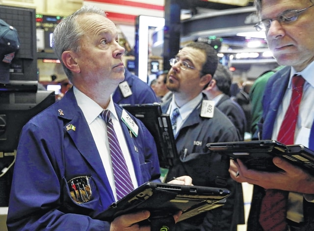Trader James Riley, left, works on the floor of the New York Stock Exchange on Tuesday. (AP Photo/Richard Drew)