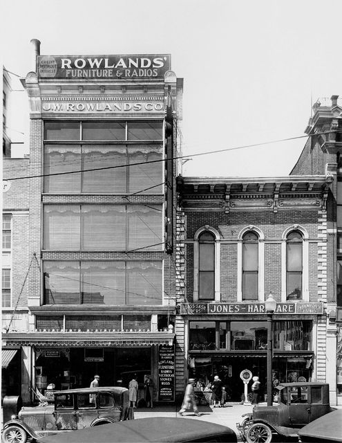 "A sign on Rowlands Furniture at street level promotes furniture, radios, Victrolas, stoves and rugs. ""The makers of happy homes"" offered credit without interest."