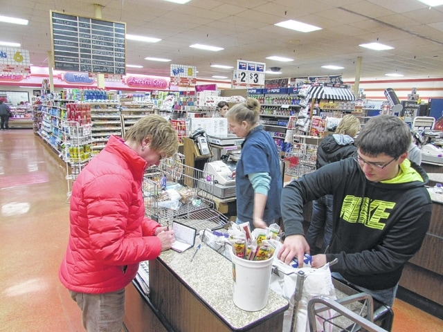 Gretchen Lammers, of Ottawa, writes out a check to pay for her groceries as Amy Hoyt, a cashier at Kohls Market in Ottawa, and Gabe Roberts, a bagger, finish checking her out during a recent weekday afternoon.