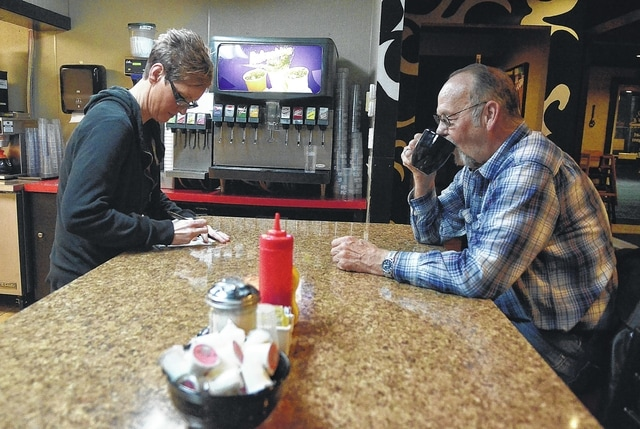 Ashlie Cumella, head waitress at LuLu's Diner on Bellefontaine Avenue in Lima, writes a breakfast order as Bob Brown enjoys his morning cup of coffee during breakfast.