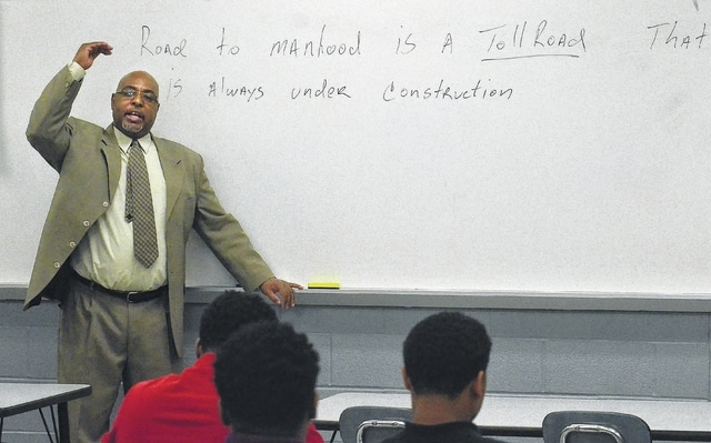 """Bryan Miller, director of Lima schools' """"Closing the Achievement Gap"""" program, explains a quote on the whiteboard, """"Road to manhood is a toll road that is always under constructions."""" CTAG, an initiative originally designed in 2007 for black males at risk of not graduating high school, expanded to help any at-risk student. When the program started, only 47 to 48 percent of black males were graduating from Lima schools. Since implementing CTAG eight years ago, that number has averaged 78 percent."""