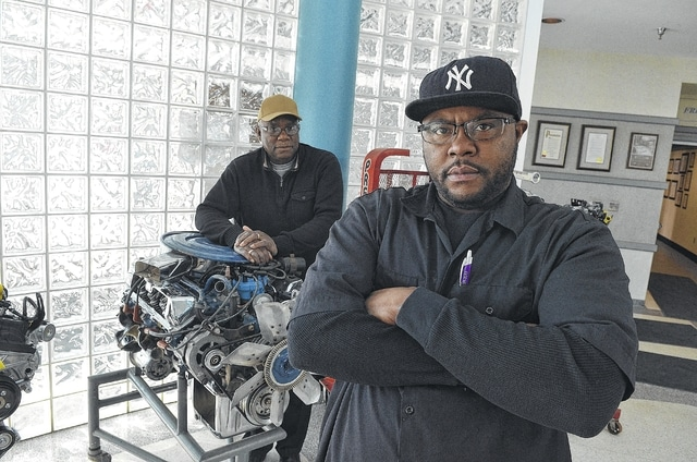 "Lydell Jackson, foreground, stands in the Ford Engine Plant education center with his father, Eugene Jackson, who retired from Ford several years ago. Lydell noted that the job market was much different for his father in the 1950s and '60s. ""My dad, he could leave one high paying job today and be in another high paying job the same day, because that was the boom of the economy. Now, the job market isn't the same. It's just not the same."""