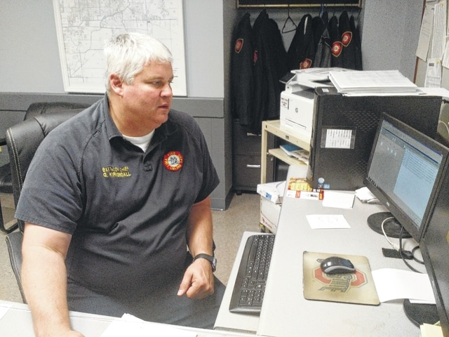 Lima Fire Department battalion chief Greg Kirkendall works on reports during the early morning hours at the department's central station.