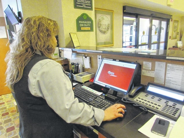 Katrina Goodwin, a guest services representative at Wingate by Wyndam in downtown Lima, works during a recent afternoon.