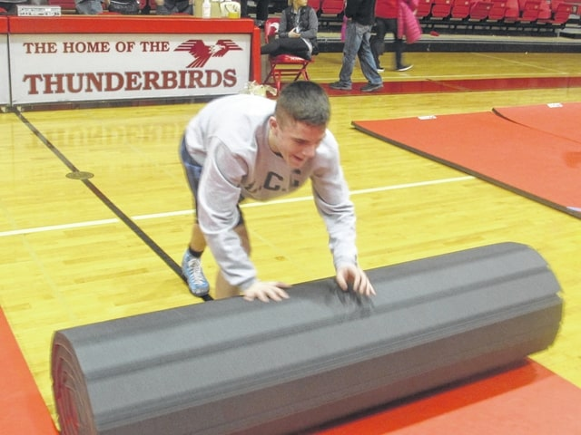 The job is only half over when Lima Central Catholic wrestlers finish a home match. The team tears down mats and puts way chairs after the event.